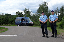 At the side of a road, in the foreground, French gendarmes and, in the background, two more with a gendarmerie van.