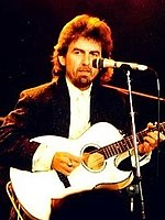 A man with long dark hair and beard, playing a white guitar