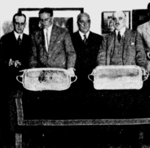 Photograph of four men, two of who are holding silver trays.