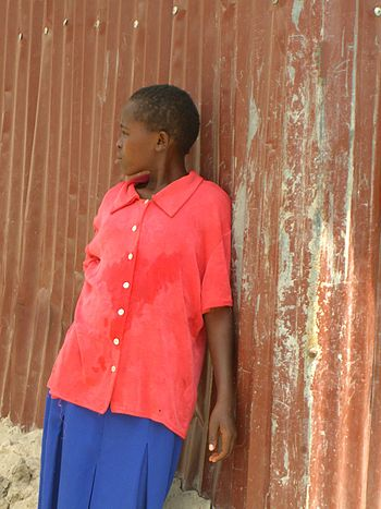 a young girl in school uniform in the slum are...