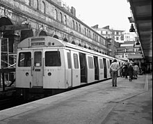 A black-and-white photograph of a silver (unpainted) electric multiple unit at a station with doors open, people walking away from camera