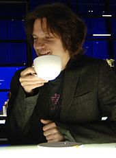 Guy Sigsworth looking towards his right and smiling, while drinking from a cup in his right hand.