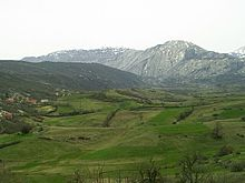 Panorama of green fields with rugged mountains in the background