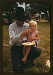 Homesteader feeding his daughter 1a34129v.jpg