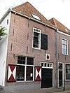 foto van Voormalig wachthuis. Gepleisterd bakstenen gebouw met schilddak. Twee leeuwenmaskers. Gevelsteen met het wapen van Edam aan de Hoogstraat