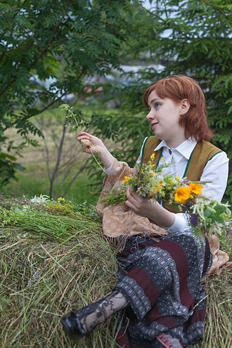 Jāņi - A girl weaving a flower wreath