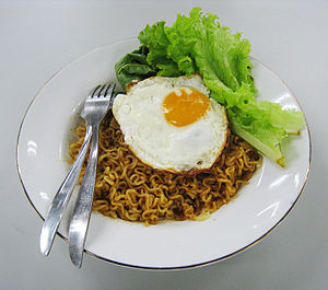 Instant noodle - A serving of Indomie Mi goreng, with fried egg and vegetables. Instant noodles need additional ingredients such as egg and vegetables to add nutritional value.