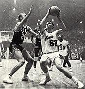 Sloan bereid om te springen met de basketbal in zijn hand en een verdediger tussen hem en het net