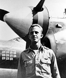 Then Maj. John Loisel standing in front of his P-38 Lightning fighter, showing Japanese flags painted on to indicate 11 kills