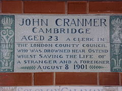 "A tablet formed of six standard sized tiles, bordered by green flowers in the style of the Arts and Crafts movement. The tablet reads ""John Cranmer Cambridge aged 23, a clerk in the London County Council who was drowned near Ostend whilst saving the life of a stranger and foreigner, August 8, 1901""."