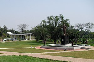Kwame Nkrumah University of Science and Technology - The main entrance of the KNUST, Kumasi and the Kwame Nkrumah Memorial Park with a statue of the first president of the Republic of Ghana and the founder of the university with five smaller figures in national attire playing drums