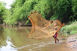 Katang youth casts fishing net in Laos