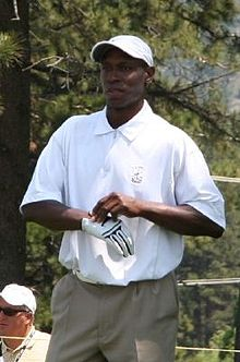 A dark-skinned man wearing a white polo shirt, white crownless baseball cap, and a white golf glove, which he is in the process of adjusting