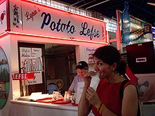 chest high portrait of a woman customer eating in front of neon-lit Lynn's Potato Lefse stand