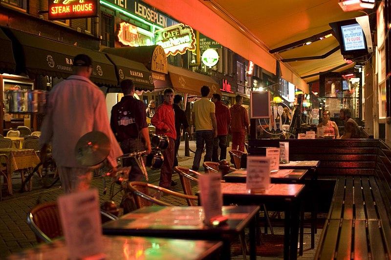 Rue proche de Leidseplein à Amsterdam : Les restaurants et les bars se succèdent sous les néons