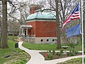 Small red brick building with a green domed roof and flags of the US and Indiana in the foreground