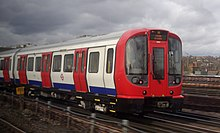 A three-quarter view of the first two coaches of an electric multiple unit running between stations, front of train and the sliding doors are red and the skirt is blue, under a grey sky