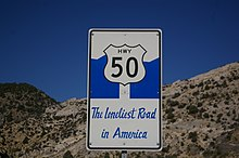 "rectangular sign with an image of a retro Highway 50 sign against a stylized blue mountain range with the words, ""The Loneliest Road in America"" written in a cursive font"