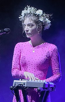Lorde playing a sampler onstage wearing a pink dress with bedazzled jewels and a flower crown on her head.