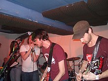 A band. On the right are two male figures (Tom and Neil Campesinos!) with guitars. Central is a male figure (Gareth Campesinos!) with a microphone. To the left is a female figure (Ellen Campesinos!) with a bass guitar. In the background a drum kit can partially be seen.