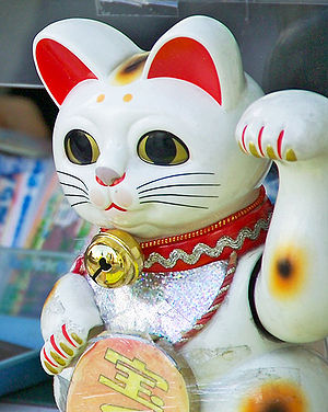 Maneki-neko - Maneki-neko with motorized arm beckons customers to buy lottery tickets in Tokyo, Japan