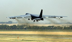 A large, grey, jet transport plane is taking off away from the camera, with the wash from the jets blurring the landscape between the aircraft and the ground.