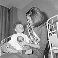 Miss Canada terwijl zij een kind op schoot heeft en het een appel aanbiedt, Bestanddeelnr 918-4770.jpg