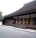 A wooden building with roofed veranda next to a raked gravel garden.