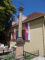 Neoclassical Memorial Cross. Listed ID 7348. Corinthian column standing on square form base. At top a iron cross. Wrougt iron fence. Now, a restaurant terrace is surrounded - Szentendre, Danube Promenade.JPG