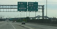 A multilane freeway approaching a bridge. In the foreground, there are two overhead green signs with the one on the left reading U.S. Route 1/U.S. Route 9 north Pulaski Skyway No Trucks next left and the one on the right reading Truck U.S. Route 1/U.S. Route 9 north New Jersey Turnpike Interstate 95 N.J. Turnpike
