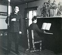 Концерт во время Войны-продолжения: Олави Вирта поёт, другой солдат играет на пианино