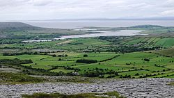 View northwest from Turlough Hill, with the Oughtmama churches at the foot of the hill, Corcomroe Abbey, two ruined castles and the Finavarra Martello Tower in the back