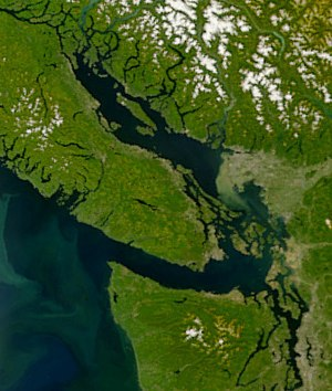 Salish Sea - The Salish Sea, showing the open Pacific Ocean at lower left, and from there, heading inland: the Strait of Juan de Fuca; Puget Sound at the lower right; heading northwards, the wide Strait of Georgia; and at the extreme northern end of that strait, Johnstone Strait. Sediment from the Fraser River is visible as a greenish plume in the Strait of Georgia.