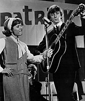 Patty Duke holds a microphone stand for Jeremy as he tunes his guitar