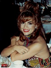 A woman sitting at a table with her arms crossed; she is wearing red lipstick and a colorful dress with sequins.