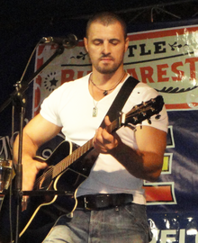 Pavel Stratan playing a guitar on stage.