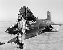 A black-and-white photo of Armstrong, with very short hair. He is smiling and is wearing a pressure suit and tall lace-up boots. Under his left arm he holds a bulky pressure helmet. He has black gloves on, and his right-hand rests on the nose of a dark-painted X-15 rocket plane with its canopy open. Armstrong and the plane are standing on a desert crust, and the plane's skids have left tracks in it.