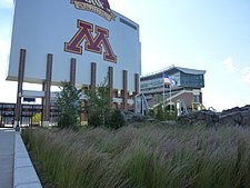 "Large sign saying ""M"", towering above a field of long grass"