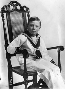 A picture of Prince John on a chair wearing a black glove.