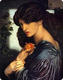Half=length portrait of a woman turned sideways, holding a pomegranate. She is wearing a blue robe and dark brown hair tumbles down her back, which is partially exposed. She has classical Roman features and bright, red lips.