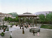 A gazebo-structure with drinking fountains at the base, in a tree-lined square.