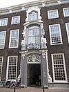 foto van PAND met Lodewijk XIV lijstgevel, vijf vensterassen breed, met rijk versierde middenrisaliet, waarin gesneden omlijstingen (ranken, klauwstukken, vrouwelijke hermen en schelpmotieven) van deur en verdiepingsvenster