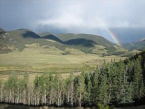 Paesaggio che mostra fiume che scorre attraverso prato verde circondato da montagne boscose