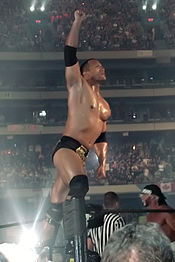 The Rock (left) poses to the crowd before his match against Hollywood Hulk Hogan (far right).