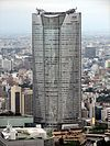 Aerial view of a gray, oval-shaped high-rise lined with rows of windows; the facade is bisected by a smaller midsection