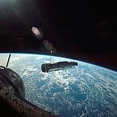 Photographie couleur du vaisseau spatial Agena dans l'espace avec la Terre en arrière-plan.