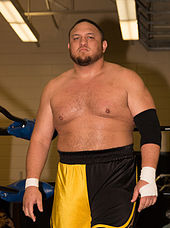 An adult Samoan male posing while wearing orange and black wrestling trunks.