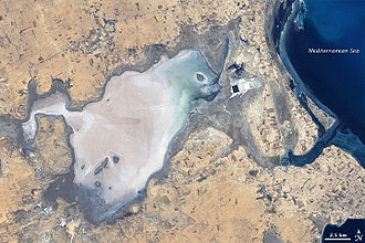 Sabkha - Sebkhat (or Sebkha) El Melah, Tunisia in 2001, mostly dry. Note rectangular industrial evaporite pans, probably for sea-salt production, upper right. Landsat 7 image.