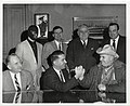 Seven unidentified men, two of which are arm wrestling and two are in costume (12932119784).jpg