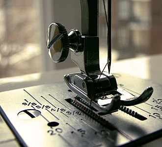 Hem - A presser foot on a home sewing machine includes measurement markings on the plate beneath the foot for easier hemming. Shown are measurements in fractions of an inch (above) and in millimetres (below).